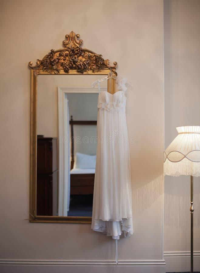 Vestido de boda y espejo adornado grande foto de archivo