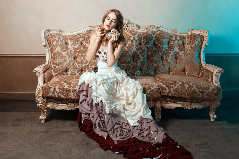 Vestido de bola da menina que senta-se nos gatinhos do sofá e do afago imagem de stock royalty free