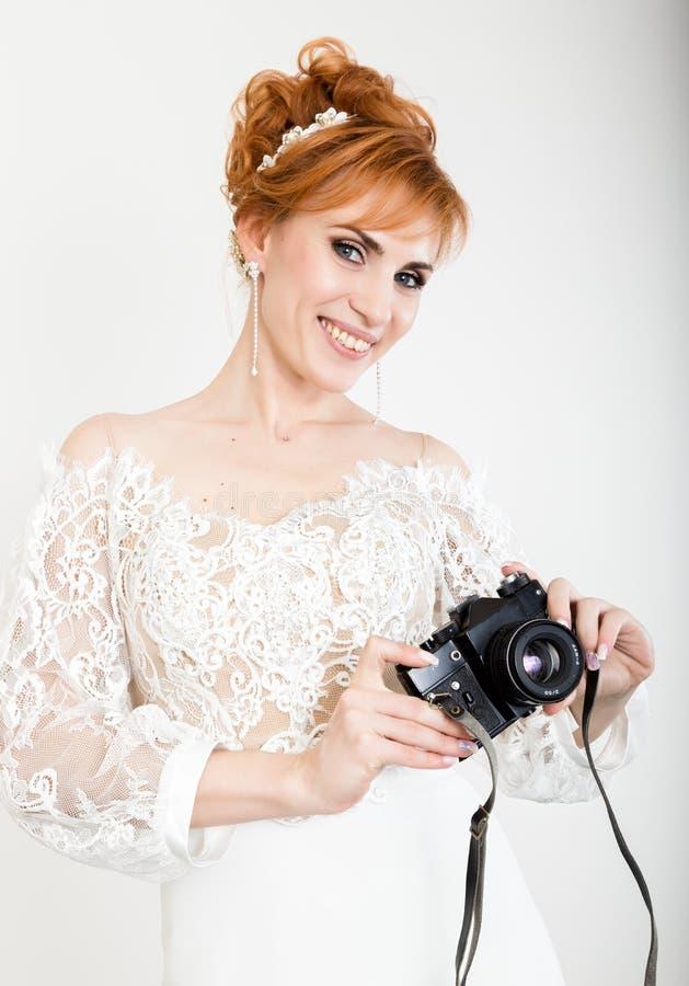 Vestido de casamento branco vestindo da noiva nova bonita do ruivo com composição e penteado profissionais Guardando a câmera imagem de stock