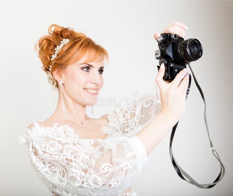 Vestido de casamento branco vestindo da noiva nova bonita do ruivo com composição e penteado profissionais Guardando a câmera foto de stock
