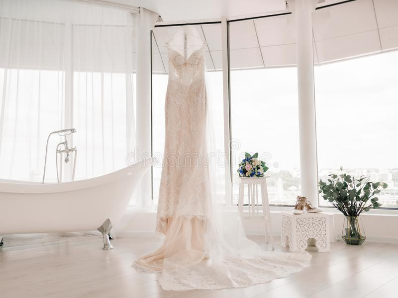 Vestido de casamento da noiva O vestido da noiva pendura em um gancho ao lado do banheiro fotos de stock royalty free