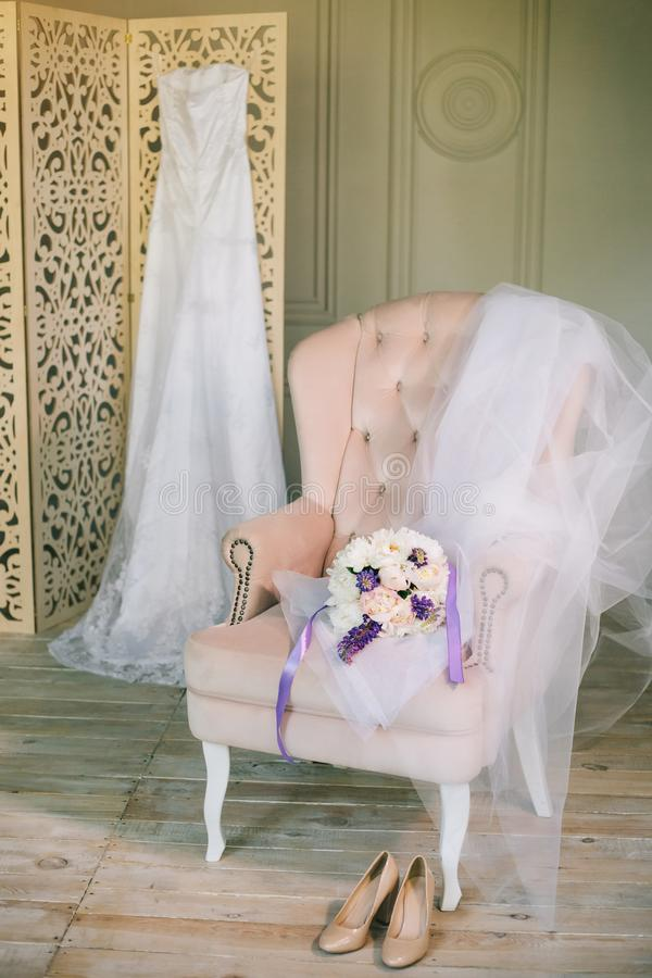 Vestido de casamento das belas artes com laço no ramalhete de dobramento da tela do armário de madeira das peônias na cadeira cor fotos de stock royalty free