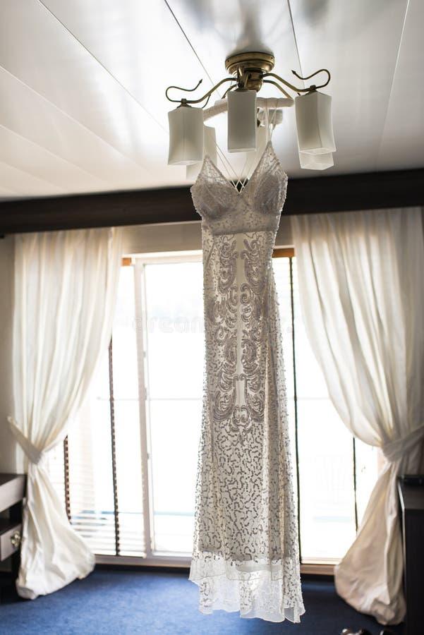 Vestido de casamento luxuoso que pendura no candelabro em uma sala de hotel Vestido nupcial bridesmaids fotografia de stock royalty free
