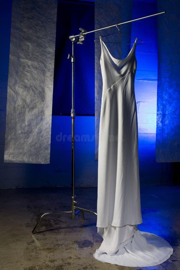 Vestido de casamento no gancho de encontro ao azul foto de stock royalty free