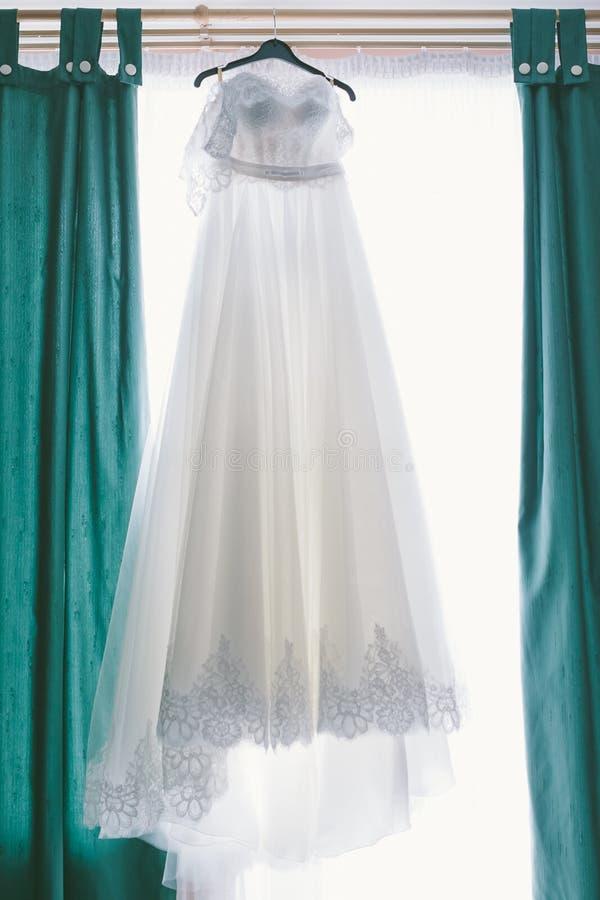 Vestido de casamento que pendura em uma janela foto de stock royalty free