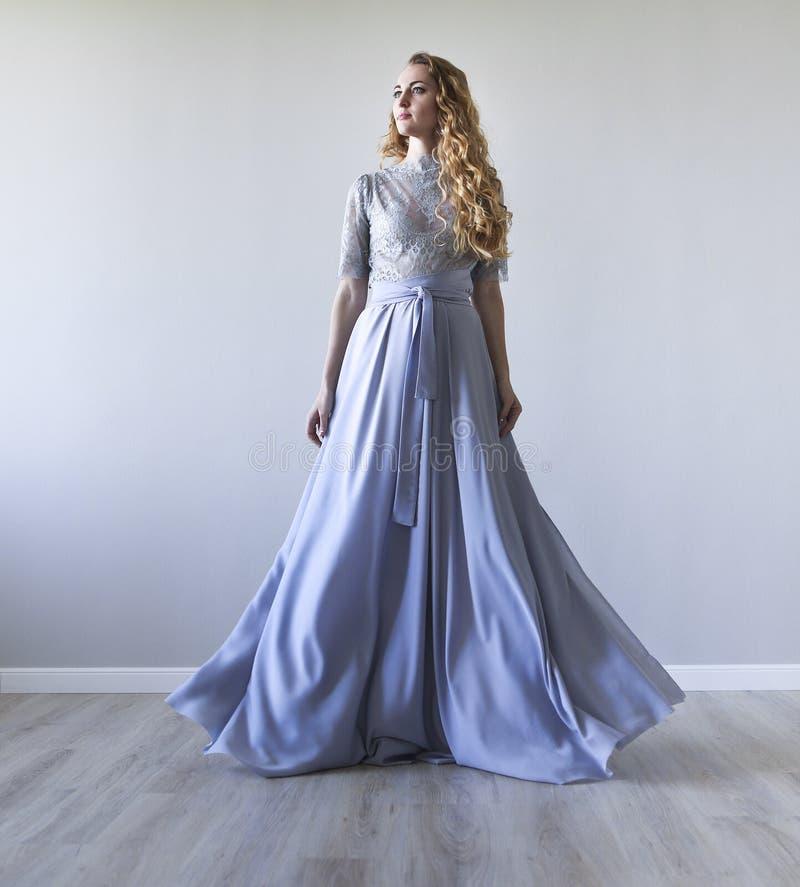 Vestido de casamento vestindo da mulher consideravelmente loura dos jovens imagens de stock