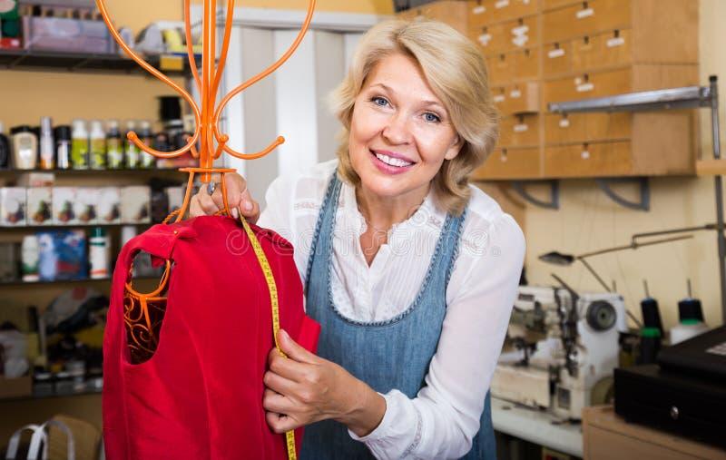 Vestido de costura de la mujer madura en taller de la ropa imagen de archivo