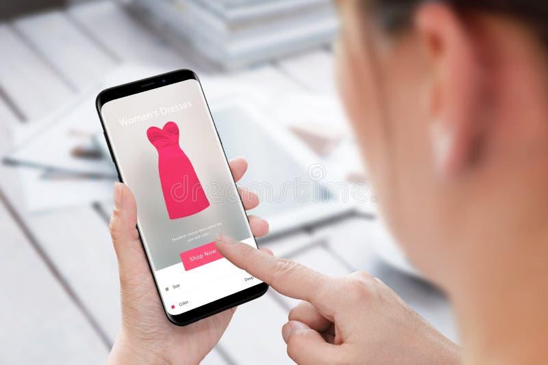 Vestido de la compra de la mujer en línea con el teléfono móvil app El hacer compras en línea imagenes de archivo