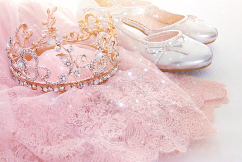 Vestido de la gasa del rosa de Tulle del vintage, corona y zapatos de la plata en piso blanco de madera imagen de archivo