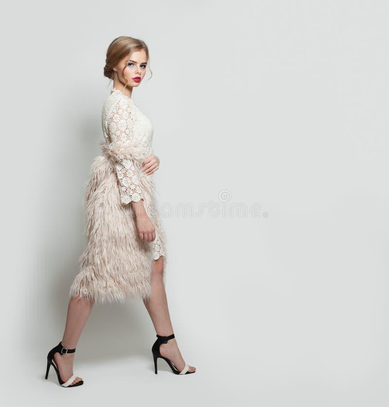 Vestido de la mujer hermosa elegante y zapatos blancos de los tacones altos que llevan en el fondo blanco fotos de archivo