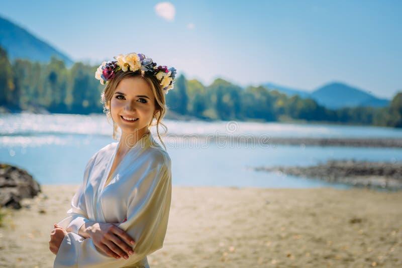 Vestido de la mujer hermosa y anillo blancos que llevan de flores en naturaleza salvaje foto de archivo libre de regalías