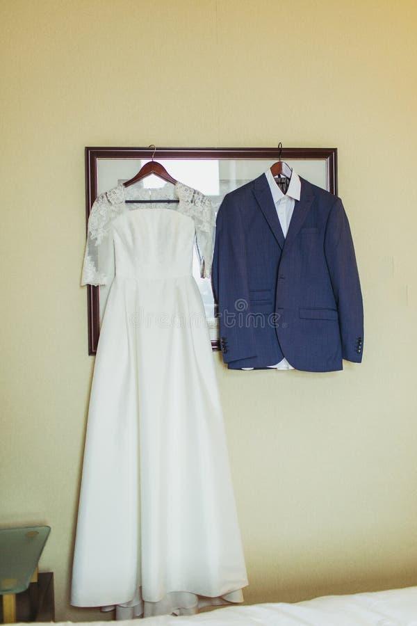 Vestido de la novia y traje del novio en vestuario dentro fotografía de archivo libre de regalías