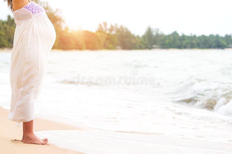 Vestido de maternidade branco do desgaste de mulher gravida que está na praia e imagem de stock