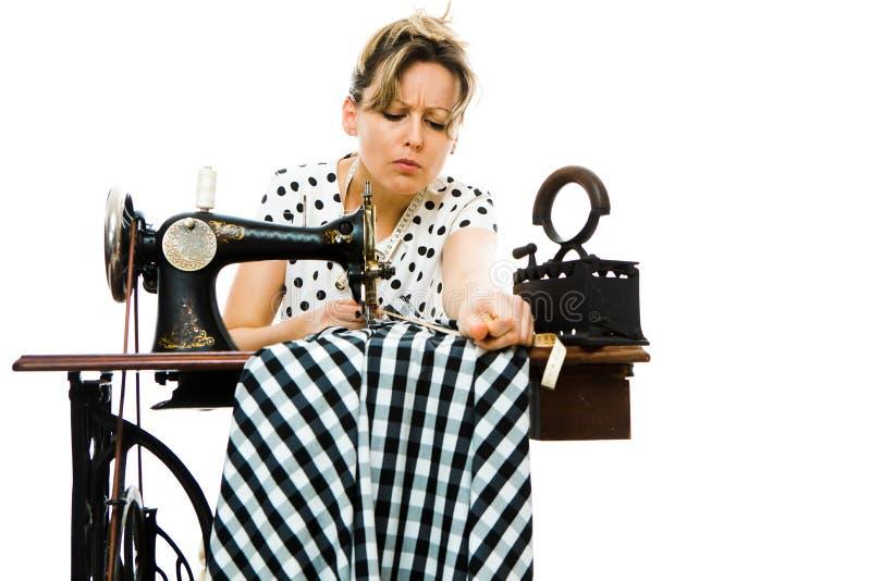 Vestido de medição da costureira da mulher antes de costurar na máquina manual velha - vintage imagem de stock