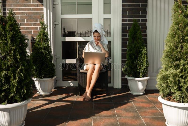 Vestido de molho vestindo da mulher moreno nova bonita feliz e toalha branca que trabalham em seu portátil da casa que senta-se s fotos de stock royalty free