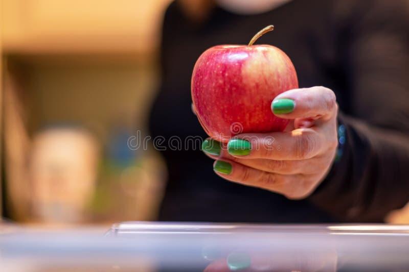 Vestido de uma mulher tirando uma maçã do frigorífico imagem de stock royalty free