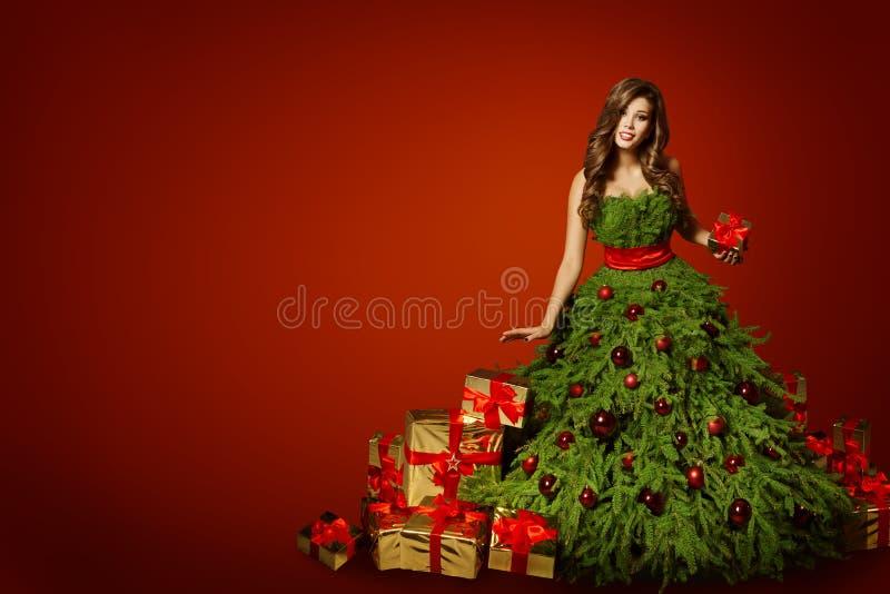 Vestido del árbol de navidad de la mujer con el actual regalo, vestido de la moda de Navidad fotografía de archivo libre de regalías