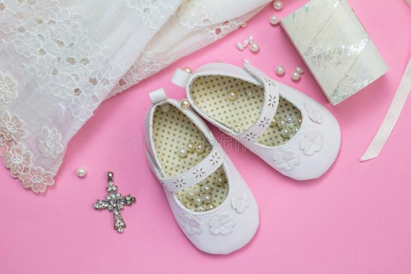 Vestido del bautismo, zapatos, colgante cruzado cristalino, perlas y pequeño m fotos de archivo