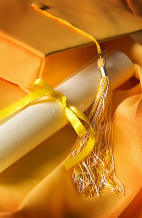 Vestido del casquillo de la graduación con el diploma fotos de archivo libres de regalías