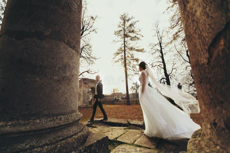 Vestido del ` s de la novia de los soplos del viento mientras que ella camina detrás de un cathedr arruinado imagen de archivo