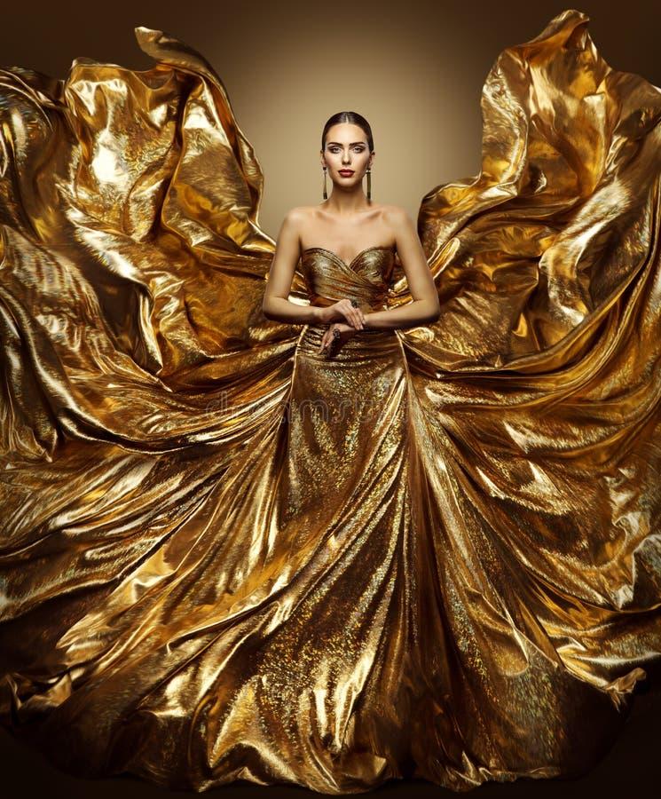 Vestido del vuelo de la mujer del oro, modelo de moda en vestido de oro del arte que agita fotos de archivo libres de regalías