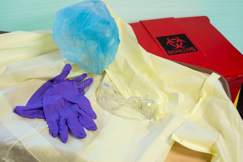 Vestido do hospital, luvas, tampa do cabelo e óculos de proteção descartáveis ao lado de imagem de stock