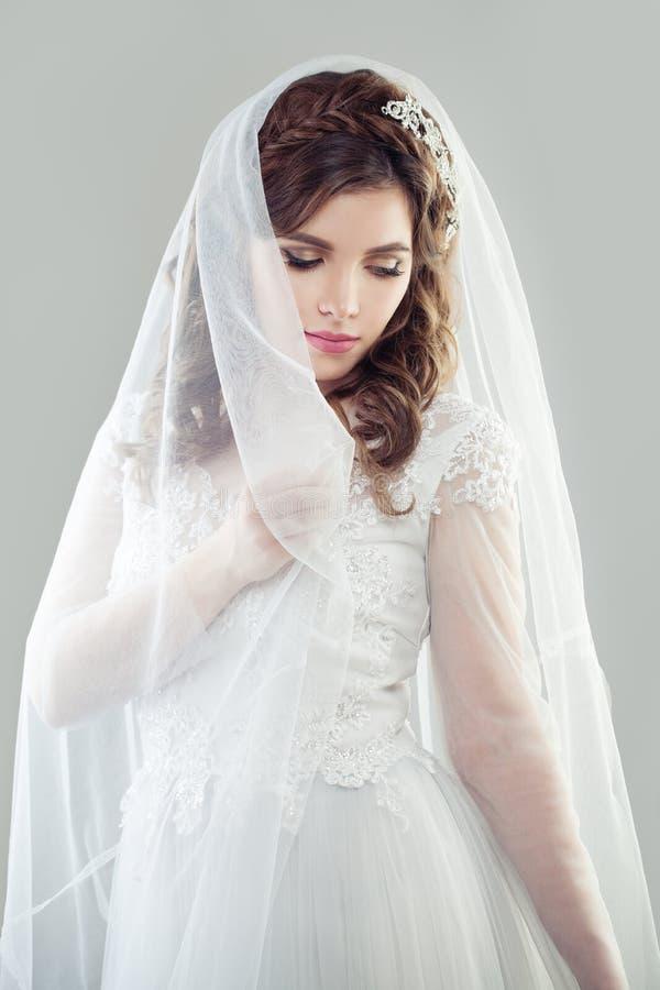 Vestido e véu nupciais brancos vestindo da mulher da noiva foto de stock royalty free