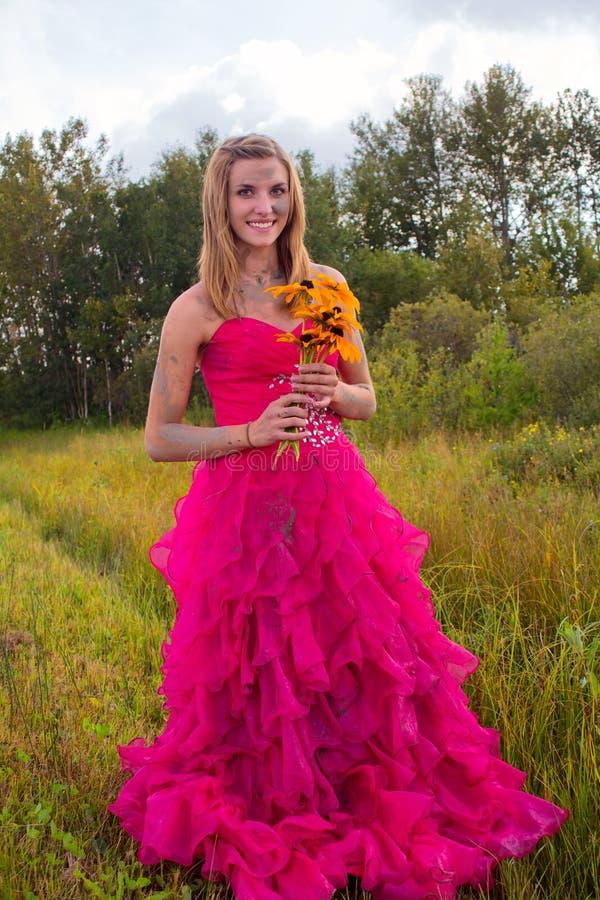 Vestido enlameado do baile de finalistas da menina que guarda flores imagem de stock royalty free