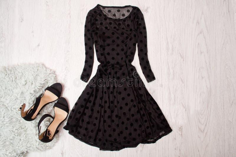 Vestido femenino negro con las mangas largas y los zapatos negros en un fondo de madera Concepto de moda, visión superior imágenes de archivo libres de regalías
