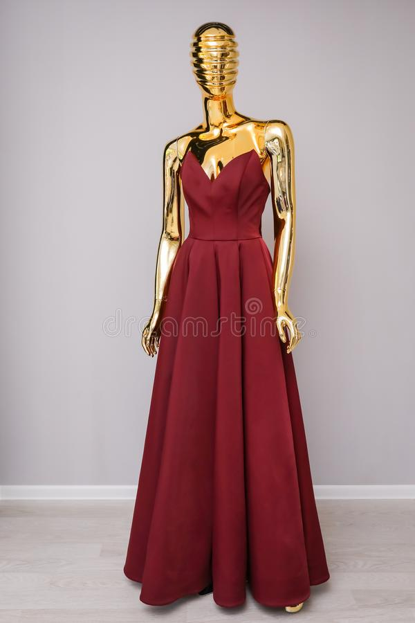 Vestido largo de la moda de Borgoña en maniquí del oro fotografía de archivo