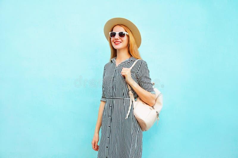 Vestido listrado vestindo de sorriso bonito da mulher, chapéu de palha do verão, trouxa que anda no azul imagem de stock