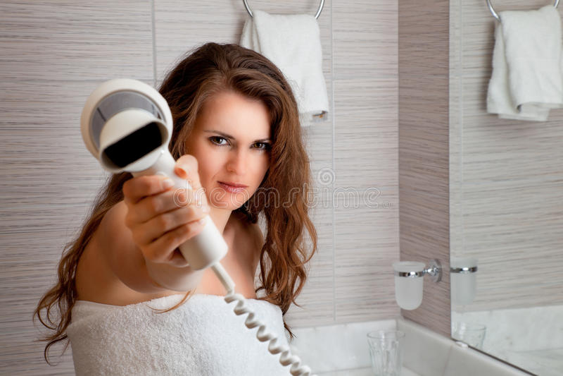 Vestido na mulher bonita de toalha que dá lhe o fen imagens de stock