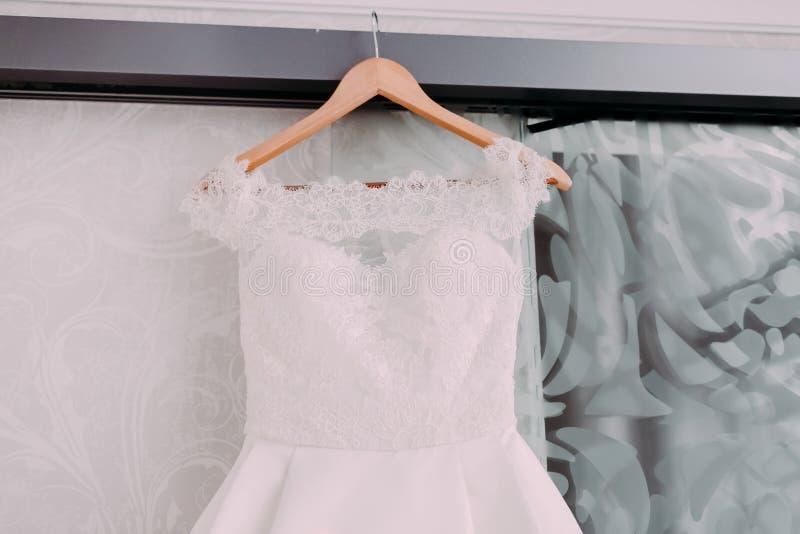 Vestido nupcial hermoso blanco con el cordón en hombros de madera, antes de la ceremonia de boda foto de archivo