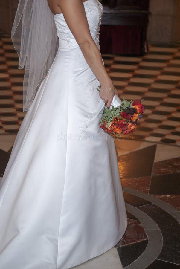 Vestido nupcial y ramo el día de boda imagen de archivo