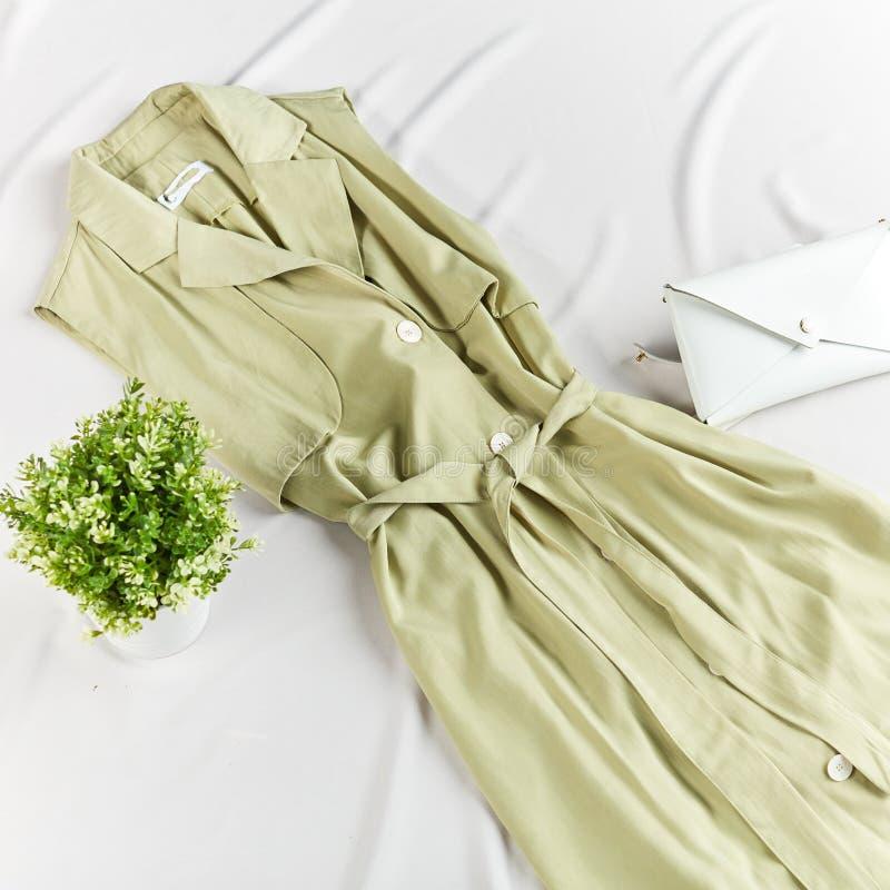 Vestido ocasional à moda elegante, saco, potenciômetro das flores na cama fotos de stock