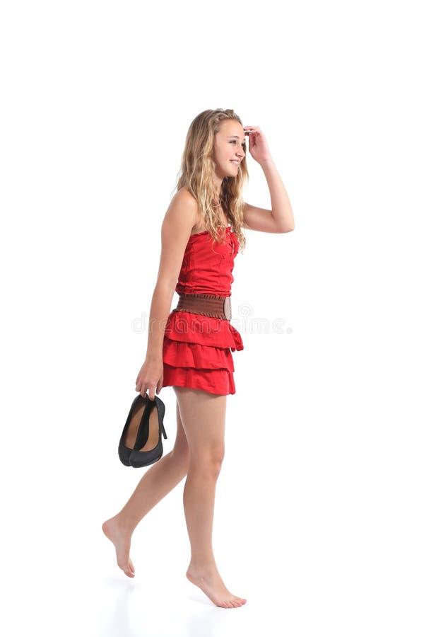 Vestido que lleva de la muchacha adolescente que camina con los talones que cuelgan de su mano imágenes de archivo libres de regalías