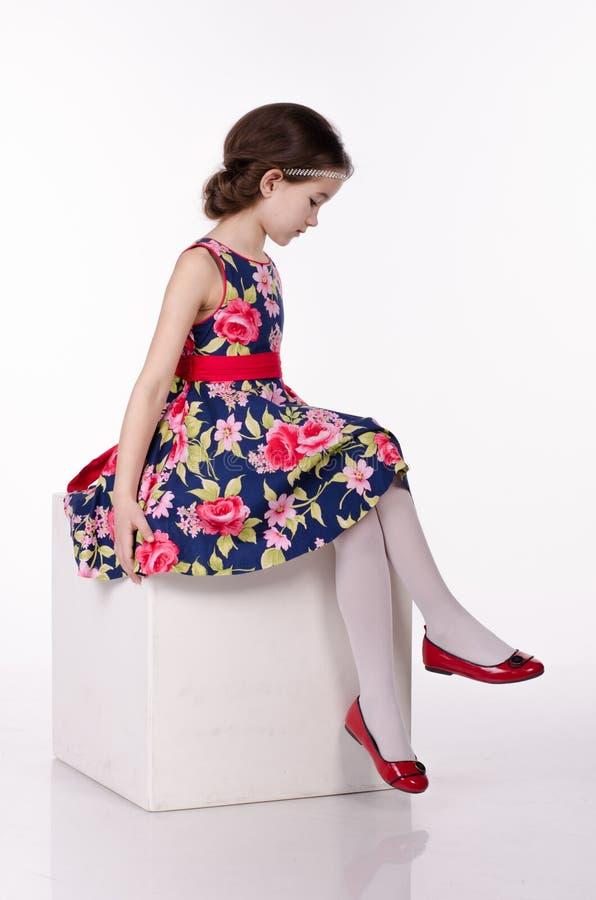 Vestido que lleva de la niña con las flores aisladas en el fondo blanco Ella se está sentando en el cubo Tiro del estudio fotos de archivo