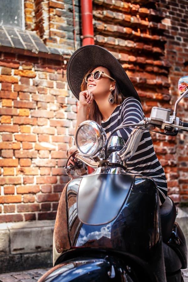 Vestido que lleva y sombrero de la mujer de moda que se sientan en una vespa italiana clásica negra en una calle vieja en Europa imágenes de archivo libres de regalías