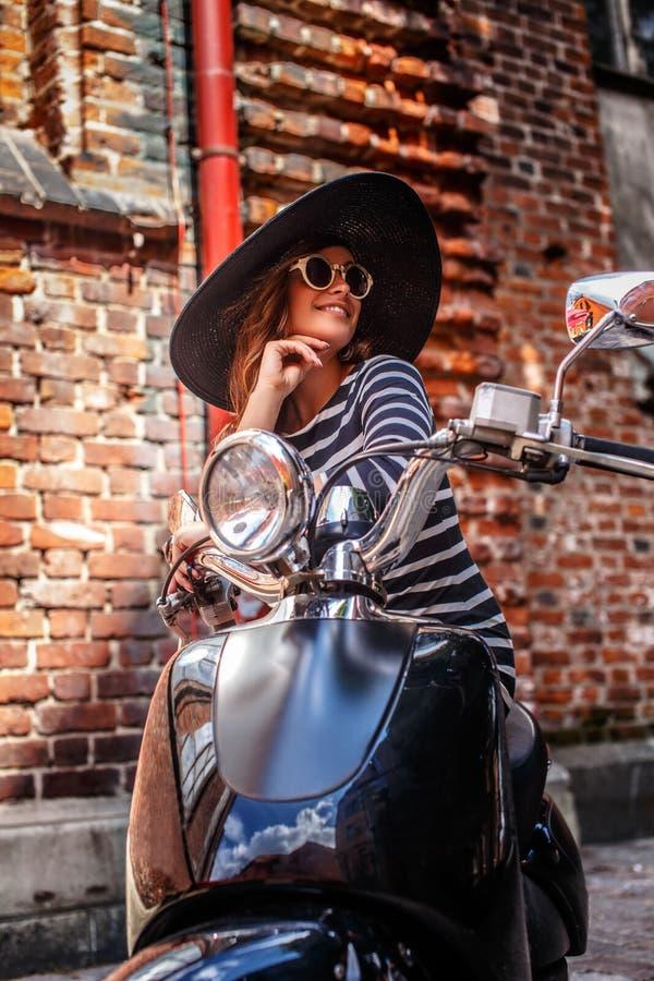Vestido que lleva y sombrero de la mujer de moda que se sientan en una vespa italiana clásica negra en una calle vieja en Europa fotos de archivo libres de regalías
