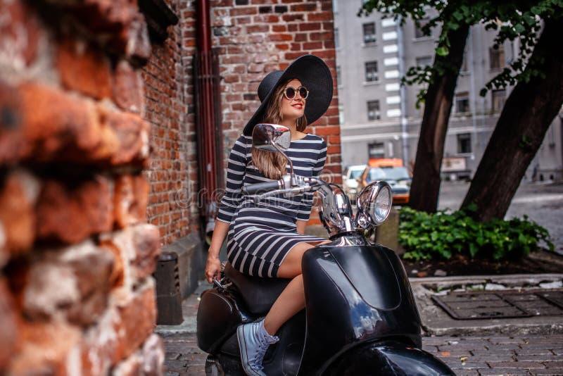 Vestido que lleva y sombrero de la mujer de moda que se sientan en una vespa italiana clásica negra en una calle vieja en Europa fotos de archivo