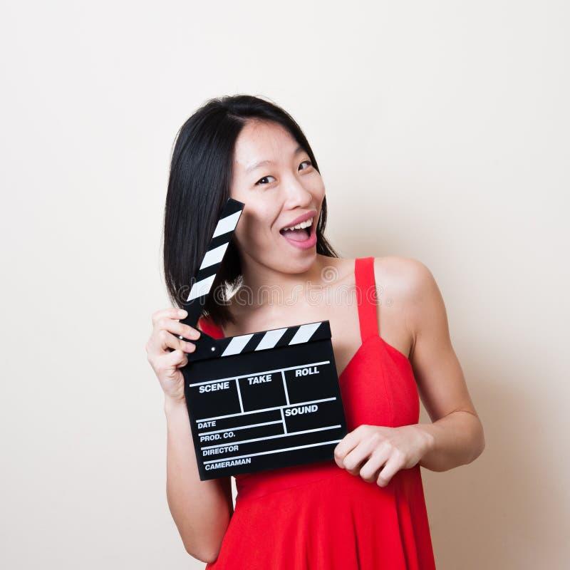 Vestido rojo de la mujer asiática divertida con clapperboard de la película en blanco fotos de archivo
