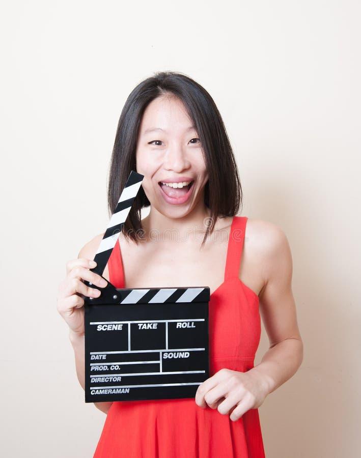 Vestido rojo de la mujer asiática divertida con clapperboard de la película en blanco foto de archivo libre de regalías