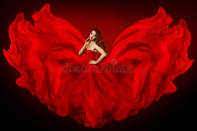 Vestido rojo de la mujer, modelo de moda en el paño que agita como alas, muchacha del vestido de seda largo en tela que agita que foto de archivo libre de regalías