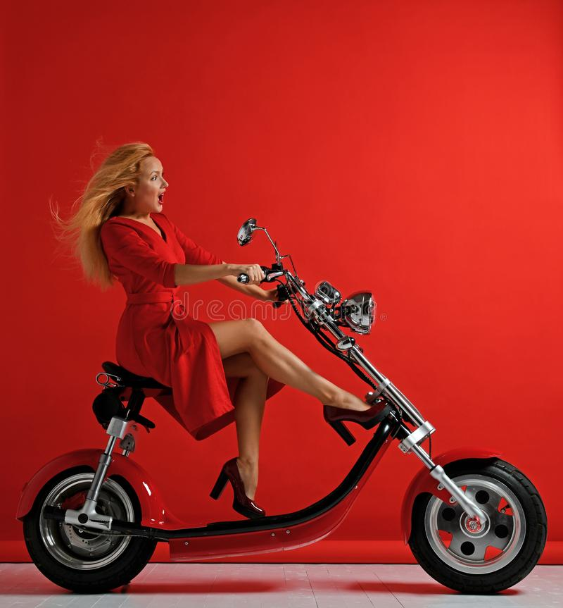 Vestido rojo de la nueva del coche eléctrico del paseo de la mujer de la motocicleta de la bicicleta bici de la vespa sorprendido foto de archivo libre de regalías