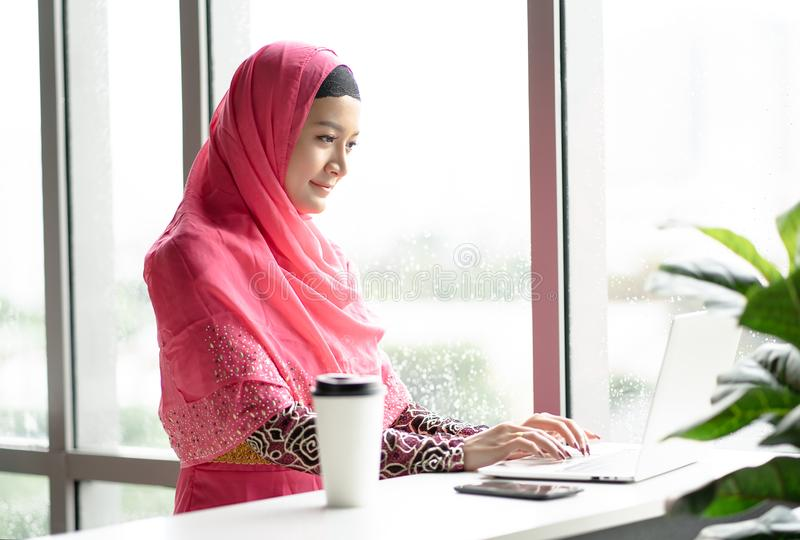 Vestido rosado del hijab de la mujer que lleva árabe joven usando el ordenador portátil que se sienta en la tabla del café Hombre fotos de archivo