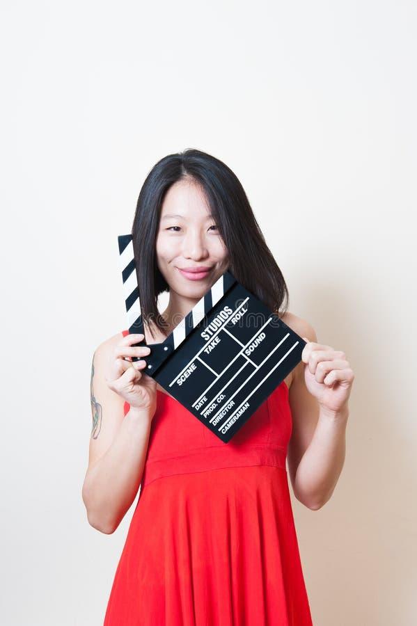 Vestido vermelho da mulher asiática bonita com placa de válvula do filme no whit foto de stock