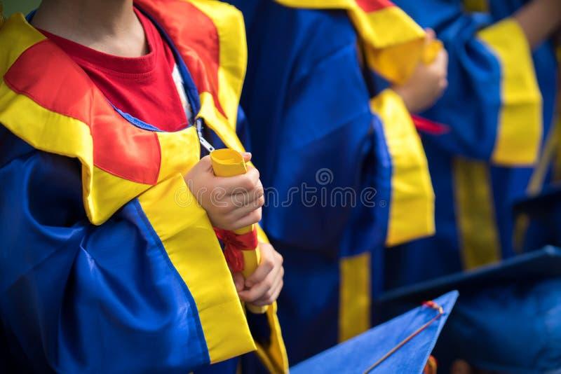 Vestido vestindo da graduação da criança pré-escolar e guardar o close up do diploma imagem de stock