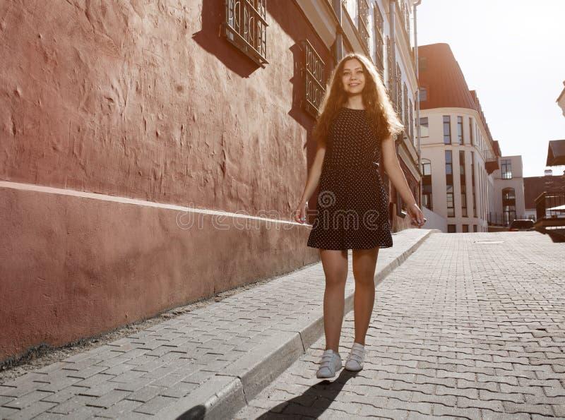 Vestido vestindo da jovem mulher moreno bonita e passeio na rua Alargamento para o texto e o projeto Estilo de vida na cidade imagem de stock