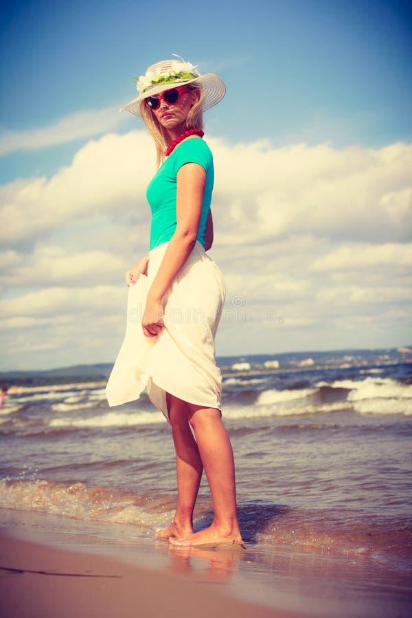 Vestido vestindo da mulher loura que anda na praia fotos de stock royalty free