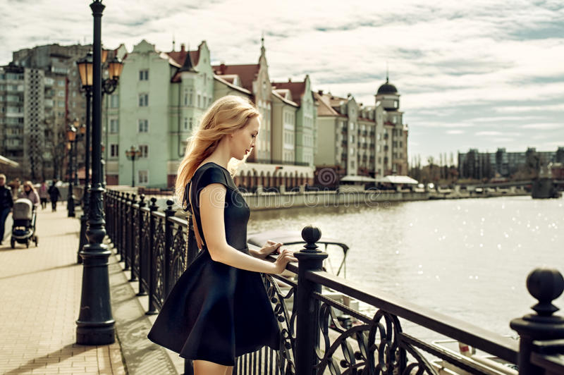 Vestido vestindo do preto da forma da jovem mulher bonita que anda no imagens de stock